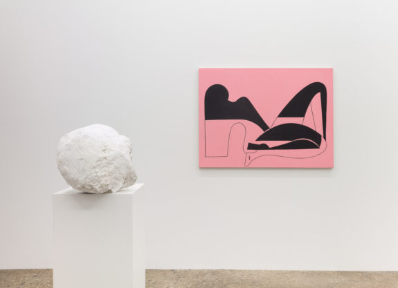 Plaster head on pedestal, pink painting of woman