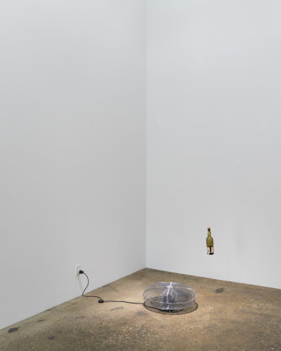 Gallery with fan on floor and suspended bottle