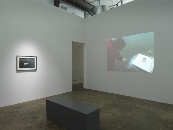 Video projection on wall, bench, framed photograph