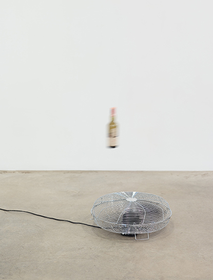 Blurry bottle suspended over fan