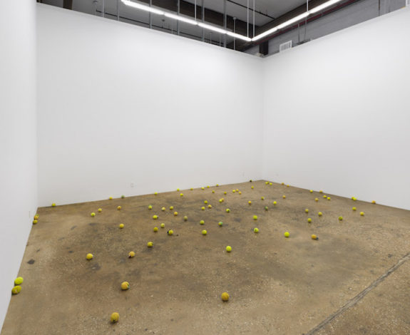 Large gallery space with tennis balls on floor