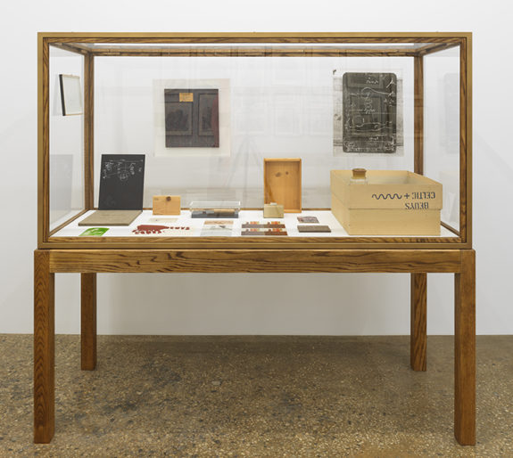 Wood and glass vitrine containing small sculptures and postcards