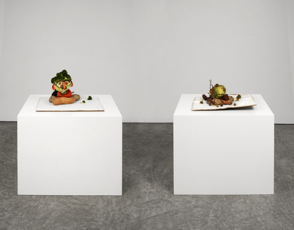 two small sculptures on pedestals
