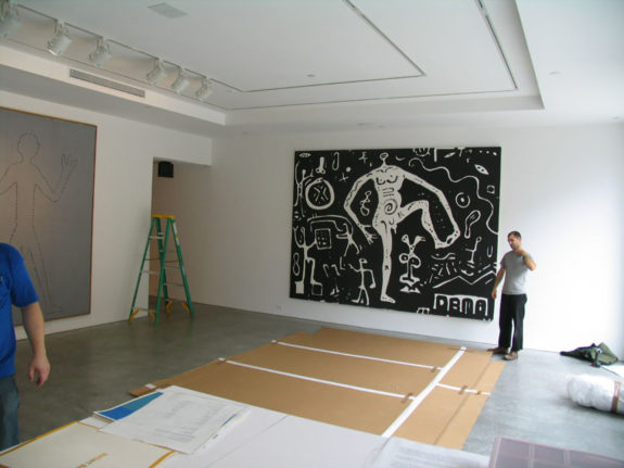 Large black painting of white figure in gallery