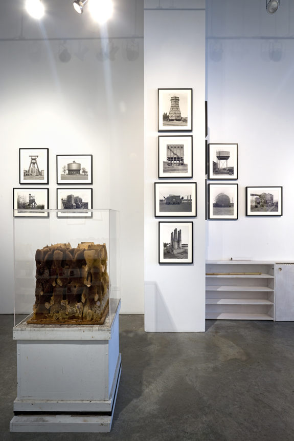 paintings and sculpture in gallery with a bookshelf
