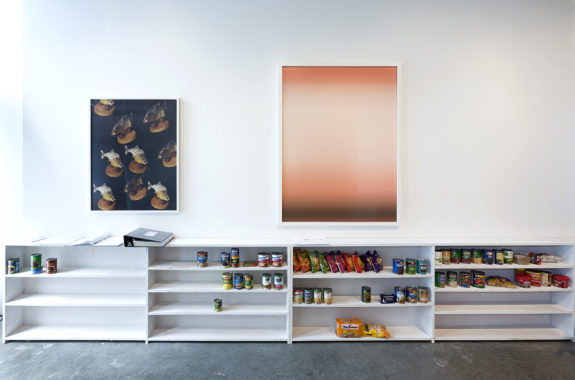 paintings in gallery above a bookshelf