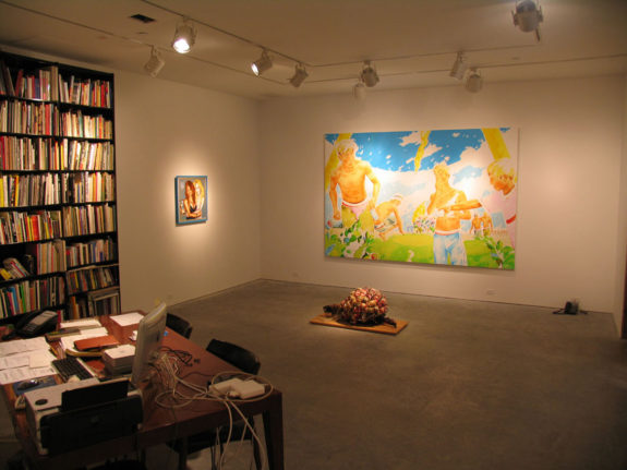 paintings and sculptures in gallery office space, large bookshelf