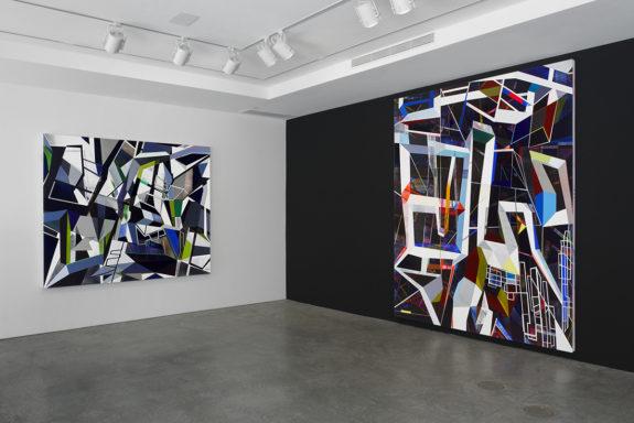 Geometric paintings in gallery on black wall