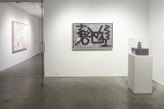 paintings in a gallery with a sculpture on a pedestal