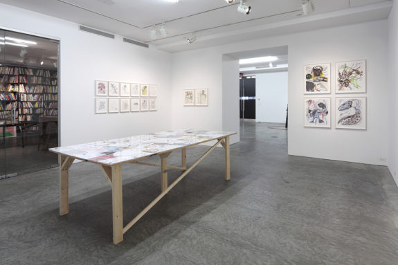 table and paintings in gallery