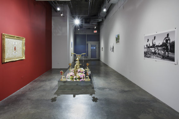 sculpture of a gold bike with flowers, a painting on a red wall and a photograph on a white wall in a gallery