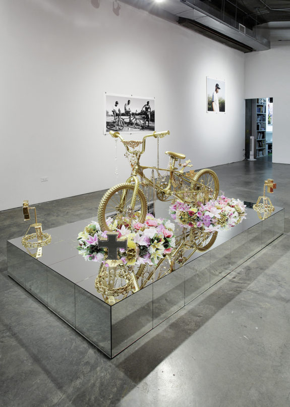 sculpture of a gold bike with flowers,