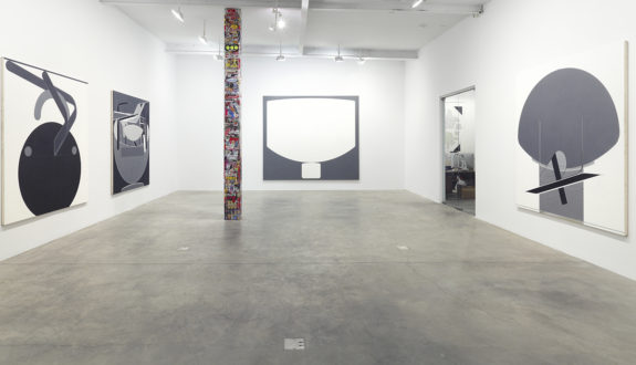 paintings in a gallery, graffiti covered pole