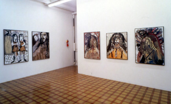5 paintings of faces in gallery