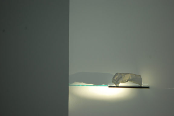 lit sculpture on a wall shelf in a gallery