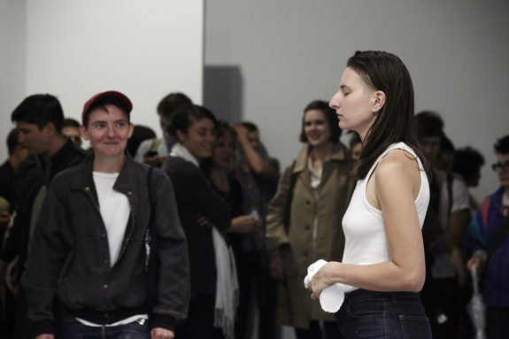 people observing a performance in a gallery