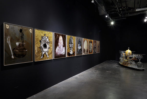 paintings hung in a line on a black wall in a gallery