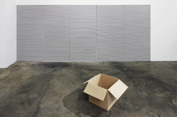 painting and a carboard box sculpture in a gallery