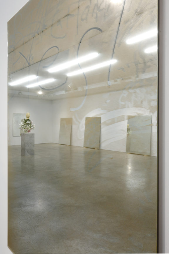 mirrored wall piece,, reflecting the sculptures within the gallery