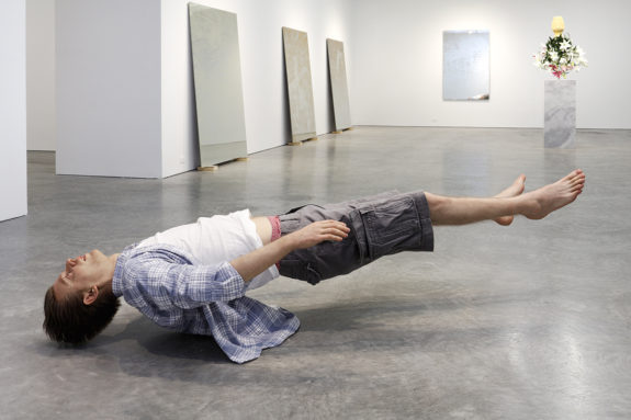 paintings and sculpture of levitating man in gallery