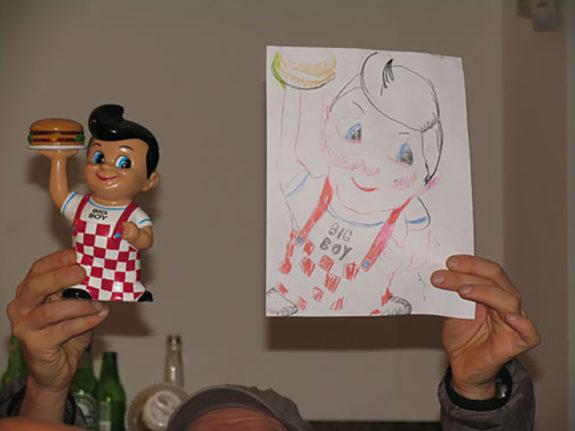 man holding up a doll and a drawing