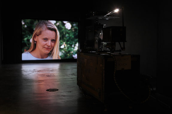 projection of a woman in a video in a dimly lit gallery