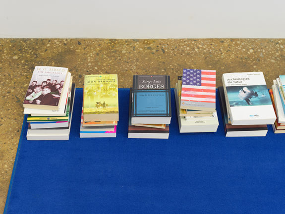 blue rug with piles of books at edges